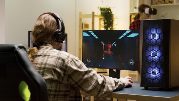 Man houdt zijn hoofd op het bureau na verlies bij videogames op de computer. game over voor mannelijke gamer.