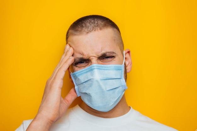 Man houdt zijn hoofd vast en geeft aan dat het pijn doet. aantrekkelijke man in een masker kijkt naar de camera. verkoudheid, griep, virus, tonsillitis, acute luchtweginfecties, quarantaine, epidemisch concept.