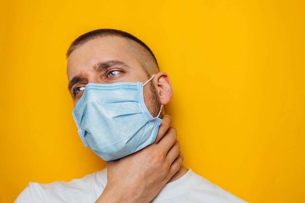 Man houdt zijn keel met zijn hand waaruit blijkt dat het pijn doet. gemaskerde man kijkt naar de camera. verkoudheid, griep, virus, quarantaine, epidemisch concept.