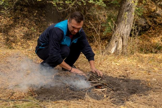 Man houten stokken in brand steken. vreugdevuur in het bos. kampvuur in de natuur
