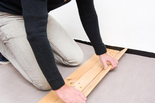 Man houten vloer zetten
