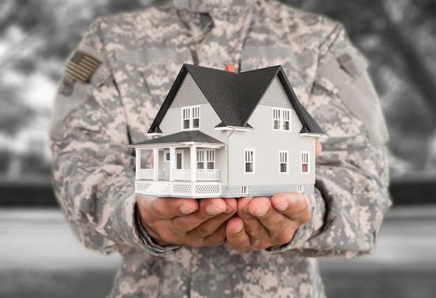 Man in amerikaans militair uniform met mock-up van huis