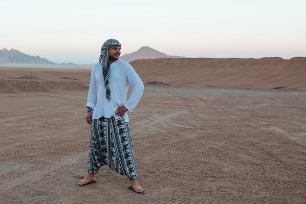 Man in arafat en bedoeïenenkleding in de woestijn op safari
