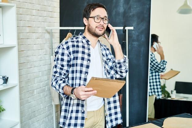 Man in atelier praten met client op telefoon