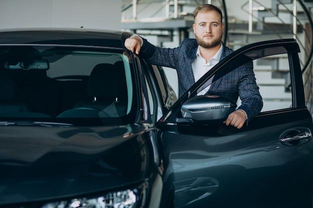 Man in autoshowroom een auto kiezen