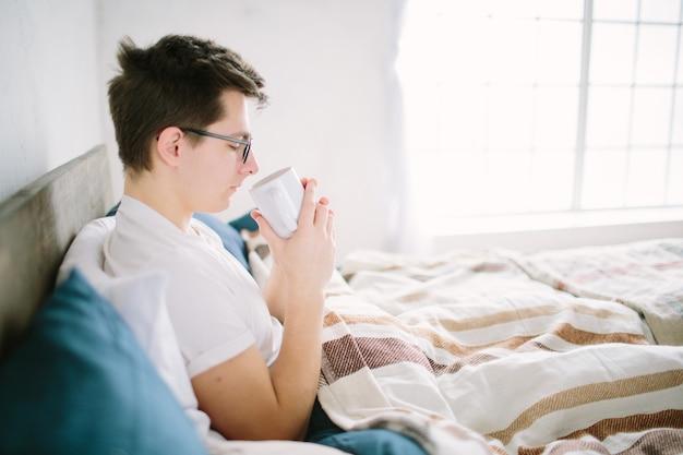 Man in bed drinken 's ochtends koffie in zonsopgang licht.