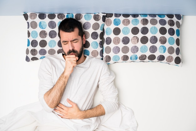 Man in bed in bovenaanzicht lijdt aan hoest en voelt zich slecht