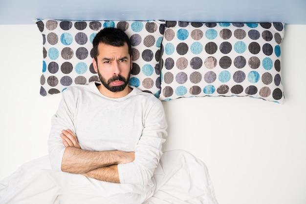 Man in bed in bovenaanzicht met droevige en depressieve uitdrukking