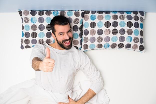 Man in bed in bovenaanzicht met duimen omhoog omdat er iets goeds is gebeurd