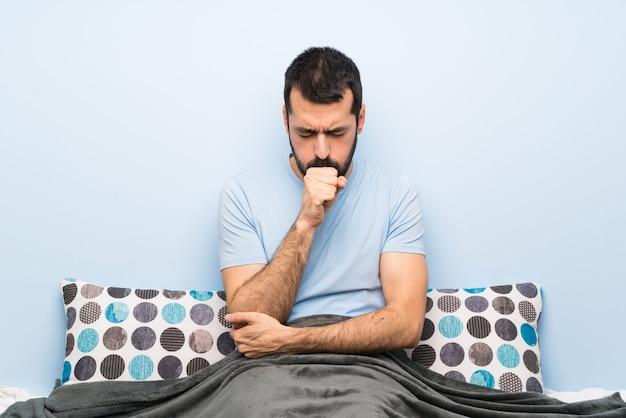 Man in bed lijdt aan hoest en voelt zich slecht