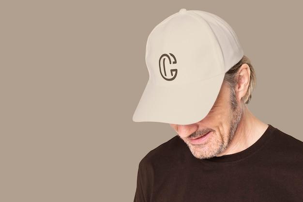 Man in beige pet met c-logo voor fotoshoot voor herenkleding