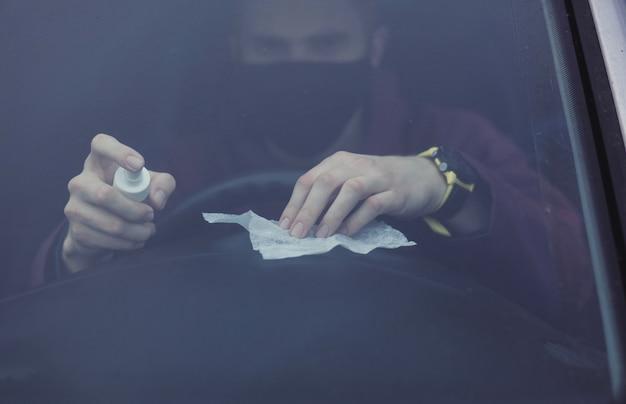 Man in beschermend masker desinfecteert de auto