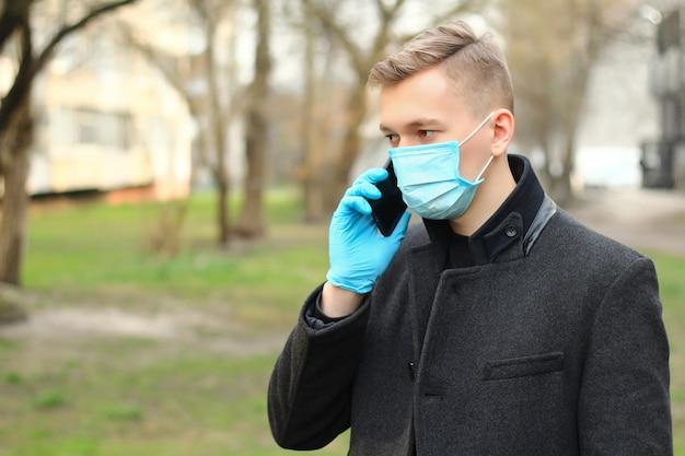 Man in beschermend masker en beschermende handschoenen praten over de telefoon