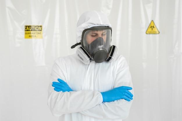 Man in beschermend pak, bril, blauwe rubberen handschoenen en gasmasker