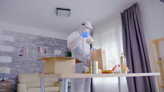 Man in beschermend pak die voedsel inpakt voor mensen in nood terwijl hij een overall, masker en andere beschermende uitrusting draagt