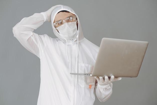 Man in beschermend pak en bril op grijze muur