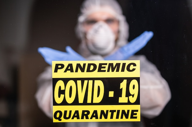 Man in beschermend pak en in beschermend medisch masker met stopgebaar. epidemioloog toont gebaar nr