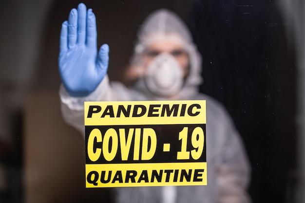 Man in beschermend pak en in beschermend medisch masker met stopgebaar. epidemioloog toont stop palm