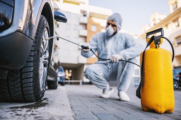 Man in beschermend pak met masker die autobanden desinfecteert, voorkomt infectie van covid-19-virus covid-19, besmetting van ziektekiemen of bacteriën. infectiepreventie en bestrijding van epidemieën. beschermende su