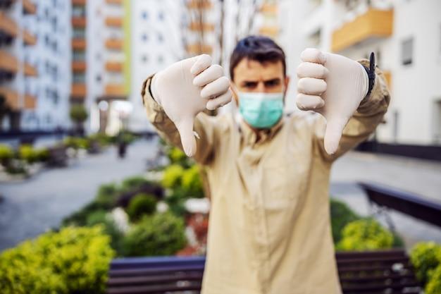 Man in beschermend pak met masker met duimen naar beneden, event infectie van virus, besmetting van ziektekiemen of bacteriën. infectiepreventie en bestrijding van epidemieën. beschermend pak