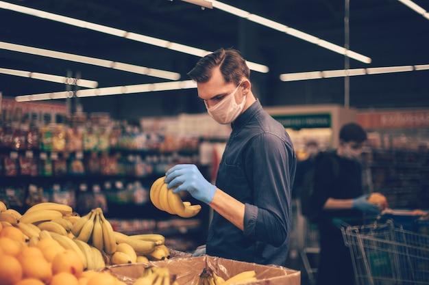 Man in beschermende handschoenen bananen kiezen in een supermarkt. hygiëne en gezondheidszorg
