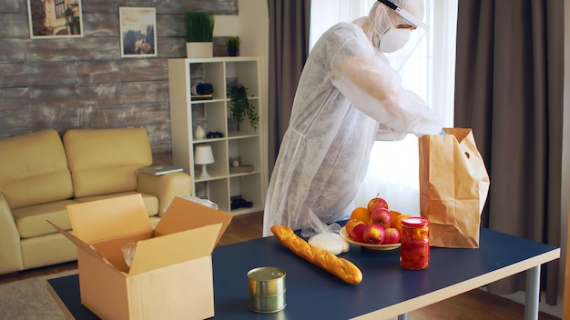 Man in beschermende handschoenen en pak die voedsel inpakt voor mensen tijdens covid-19 pandemie.