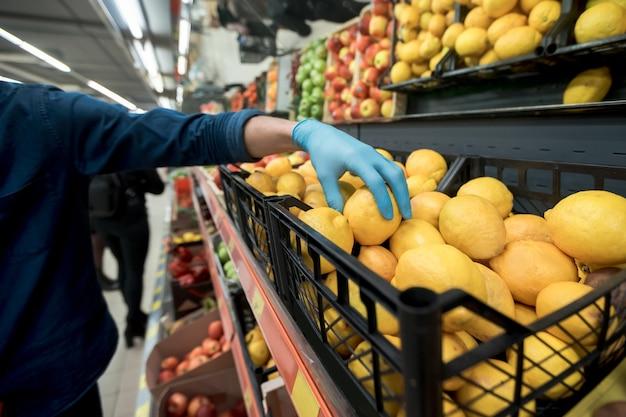 Man in beschermende handschoenen pakt een citroen uit een supermarkt. foto met een kopie-spatie