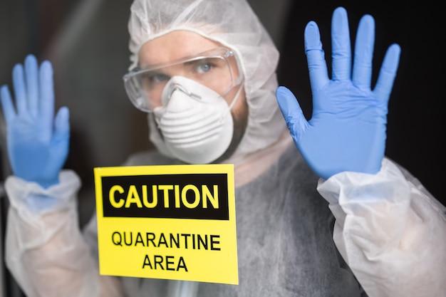 Man in beschermende witte overall, masker en bril op zijn gezicht. coronavirus, pandemie, covid-19, griep