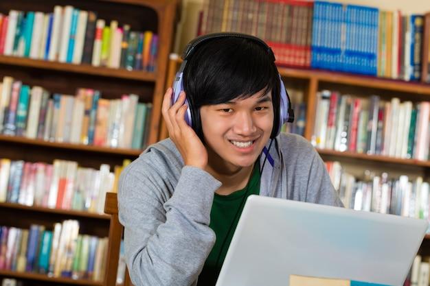 Man in bibliotheek met laptop en koptelefoon