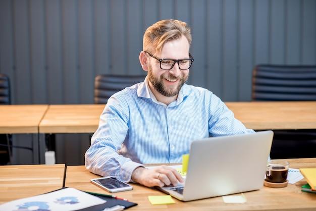 Man in blauw shirt aan het werk met laptop in het moderne kantoorinterieur