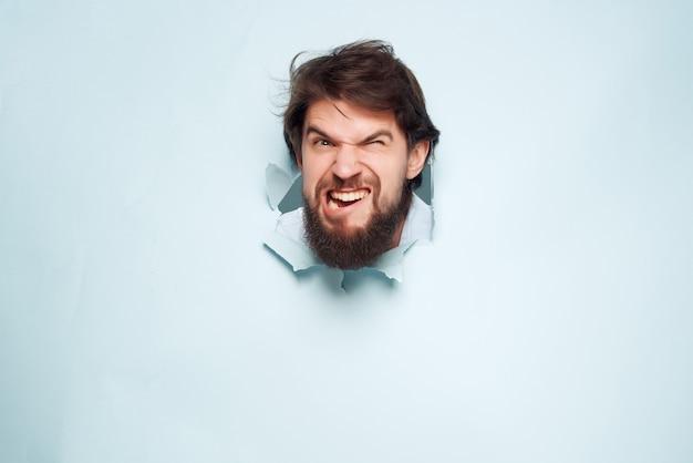 Man in blauw shirt breekt door de achtergrond leuke geïsoleerde achtergrond. hoge kwaliteit foto