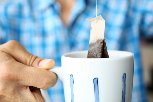 Man in blauw shirt kopje thee maken met behulp van moderne handige theezakje