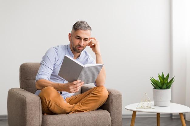 Man in blauw shirt leest uit een boek