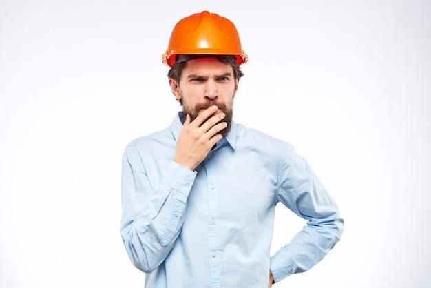 Man in blauw shirt oranje helm professionele bouwveiligheid ingenieur