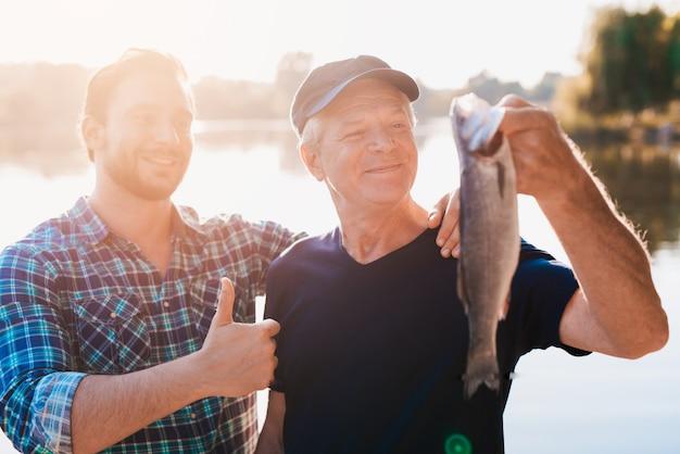 Man in blauw shirt staat naast hem met een duim omhoog.