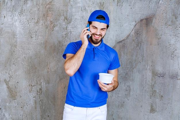 Man in blauw uniform met een afhaalmaaltijden plastic beker en praten met de telefoon.