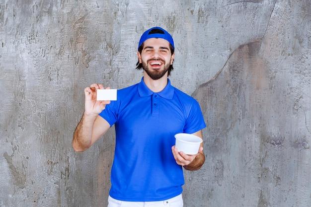 Man in blauw uniform met een plastic beker om mee te nemen en zijn visitekaartje te presenteren.