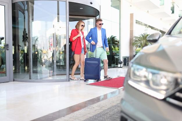 Man in blauwe jas draagt koffer in auto.