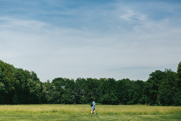 Man in blauwe korte broek lopen langs het groene gazon