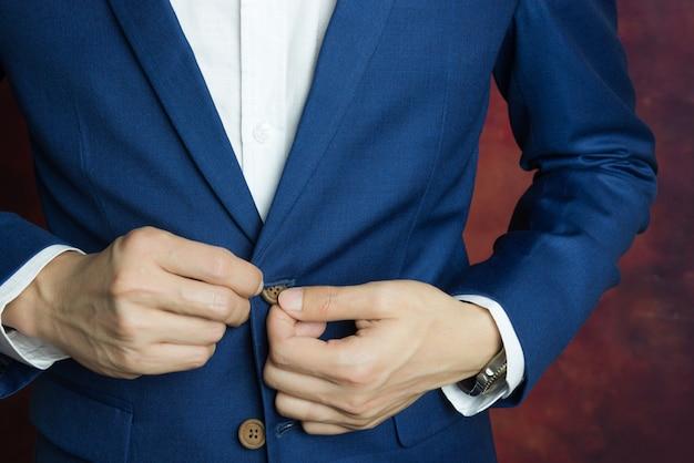 Man in blauwe pak, knop doen