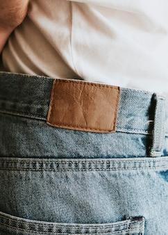 Man in blauwe spijkerbroek met bruine tag