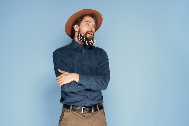 Man in bloemen hoed in baard emoties ecologie stijl blauwe muur.