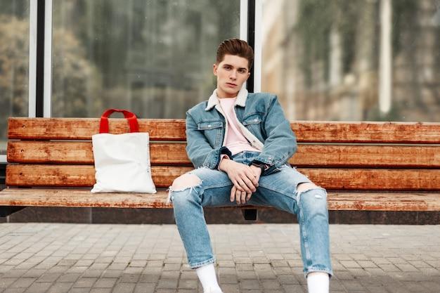 Man in blue fashion denim uitloper met jeans zit op houten bankje