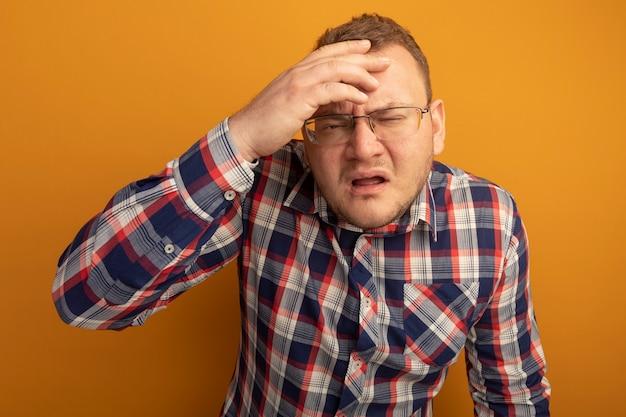 Man in bril en geruit overhemd verward met hand boven het hoofd fronsen staande over oranje muur