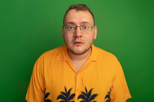 Man in bril en hawaiiaans overhemd die verward en zeer angstig over groene muur staan