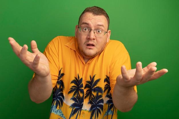Man in bril en oranje overhemd verward met opgeheven armen zonder antwoord staande over groene muur