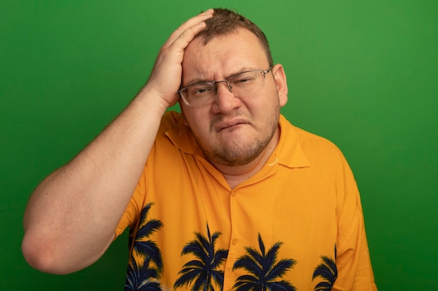 Man in bril en oranje overhemd verwarde purding lippen met hnad op zijn hoofd voor fout staande over groene muur