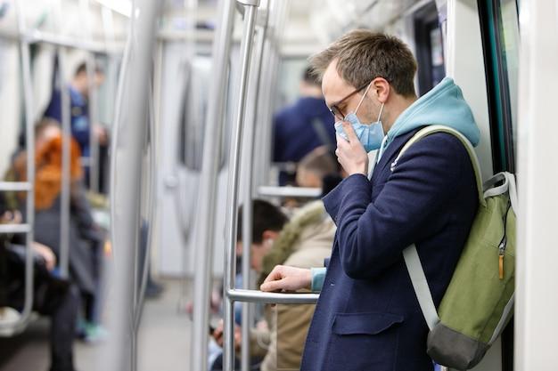 Man in bril, hoestend, met beschermend masker tegen overdraagbare infectieziekten en als bescherming tegen coronavirus