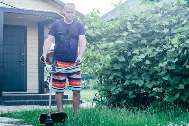 Man in bril, korte broek en t-shirt maait gazon met benzinetrimmer, tegen de achtergrond van de wijngaard en de ingang van het huis