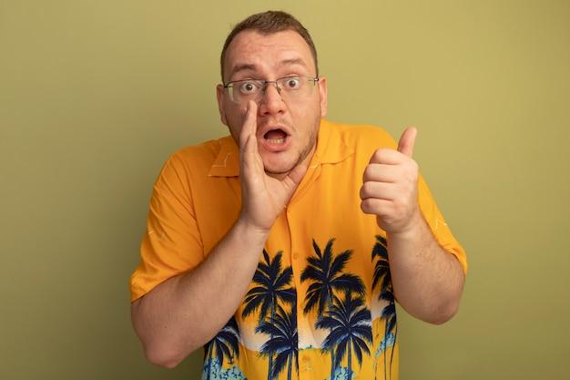 Man in bril met oranje overhemd verrast wijzend hand in de buurt van de mond staande over lichte muur